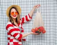 Smiling woman in hat and striped jacket with net bag. Portrait of a young smiling woman in hat and striped jacket with net bag on checkered background royalty free stock image