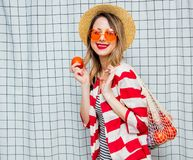 Smiling woman in hat and striped jacket with net bag. Portrait of a young smiling woman in hat and striped jacket with net bag on checkered background stock image