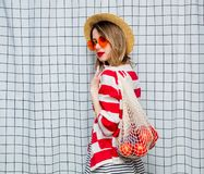 Smiling woman in hat and striped jacket with net bag. Portrait of a young smiling woman in hat and striped jacket with net bag on checkered background royalty free stock photography