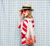 Smiling woman in hat and striped jacket with net bag. Portrait of a young smiling woman in hat and striped jacket with net bag on checkered background stock photos