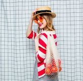 Smiling woman in hat and striped jacket with net bag. Portrait of a young smiling woman in hat and striped jacket with net bag on checkered background royalty free stock images