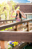 Smiling woman in hat walking over the wooden bridge at sunny day Stock Images
