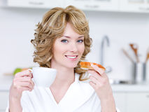Smiling woman having breakfast Royalty Free Stock Image