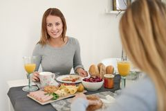 Smiling woman having breakfast with her daughter Stock Photography