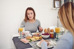 Smiling woman having breakfast with her daughter Stock Images