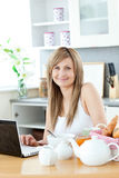 Smiling woman having breakfast in the kitchen Stock Image