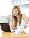 Smiling woman having breakfast using her laptop Royalty Free Stock Photography