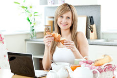 Smiling woman having breakfast using her laptop Stock Photo