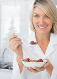 Smiling woman having cereal for breakfast Royalty Free Stock Image