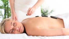 Smiling woman having a hot stone massage Royalty Free Stock Photo