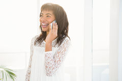 Smiling woman having a phone call in living room Stock Photos