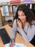 Smiling woman having a phone conversation sat at her desk Royalty Free Stock Photos