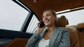Smiling woman having phone talk in taxi. Businesswoman talking phone at car