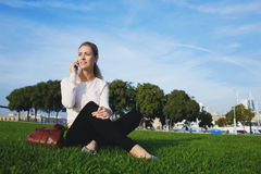 Smiling woman having a pleasant conversation on smart phone while enjoying sun and good day during recreation time Royalty Free Stock Photography