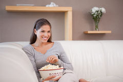 Smiling woman having popcorn while watching a movie Stock Photo