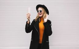 Smiling woman having video call or taking selfie by smartphone. People, technology and communication concept - smiling woman having video call or taking selfie stock photo