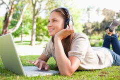 Smiling woman with headphones and a laptop lying on the lawn Stock Image