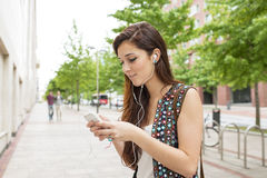 Smiling woman with headphones listening music, in the street. Royalty Free Stock Photography