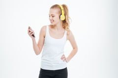 Smiling woman in headphones listening to music from cell phone Stock Photos