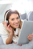 Smiling woman with headphones and tablet Stock Images