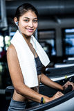 Smiling woman with headphones using treadmill Stock Photos