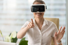 Smiling woman in headset enjoying VR tour, touching virtual worl. Smiling woman in VR headset enjoying virtual tour, pointing by finger at augmented world Stock Photography