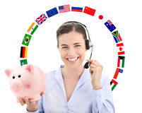 Smiling woman with headset, flags and piggy bank, transfer money Royalty Free Stock Image