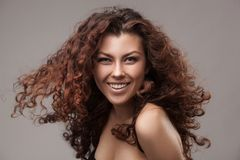 Smiling woman with healthy brown curly hair Stock Photography