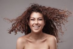 Smiling woman with healthy brown curly hair Stock Images