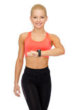 Smiling woman with heart rate monitor on hand Royalty Free Stock Photos