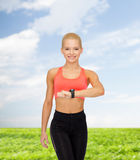 Smiling woman with heart rate monitor on hand Stock Image