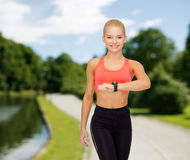 Smiling woman with heart rate monitor on hand Royalty Free Stock Photography