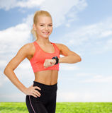 Smiling woman with heart rate monitor on hand Royalty Free Stock Image