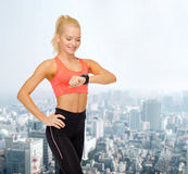 Smiling woman with heart rate monitor on hand Stock Images