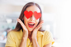 Smiling woman with the hearts on her eyes. Emoji concept: woman with the hearts instead of her eyes royalty free stock images