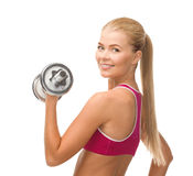 Smiling woman with heavy steel dumbbell Royalty Free Stock Photos