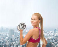 Smiling woman with heavy steel dumbbell Royalty Free Stock Images