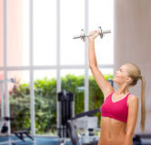 Smiling woman with heavy steel dumbbell Stock Photo