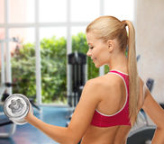 Smiling woman with heavy steel dumbbell at gym Royalty Free Stock Photos
