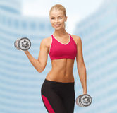 Smiling woman with heavy steel dumbbells Royalty Free Stock Photo
