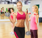Smiling woman with heavy steel dumbbells Stock Photo