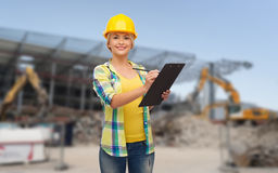 Smiling woman in helmet with clipboard Stock Image