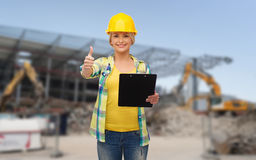 Smiling woman in helmet with clipboard Royalty Free Stock Photos