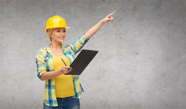 Smiling woman in helmet with clipboard stock photo