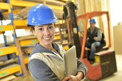 Smiling woman with helmet working in warehouse Royalty Free Stock Image