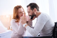 Smiling woman helping her man drink tea. Helping her love. Attractive alive blond women and a bearded men smiling and the women giving tea to him while the men Stock Photography