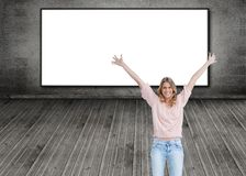 Smiling woman with her arms raised up. Composite image of smiling woman with her arms raised up standing in front of screen Royalty Free Stock Photo