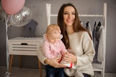 Smiling woman and her cute little daughter holding a present royalty free stock photo