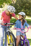 Smiling woman with her daughter riding bicycles Royalty Free Stock Images