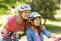 Smiling woman with her daughter riding bicycles Stock Images